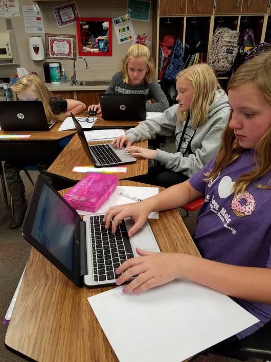 Teacher Ashley Gustin student writing on laptop for Studentreasures